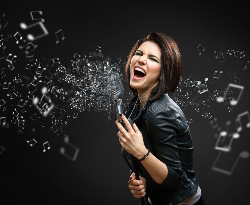 Kobieta rockowy muzyk trzyma brzmiącego mike z melodią w powietrzu obraz stock