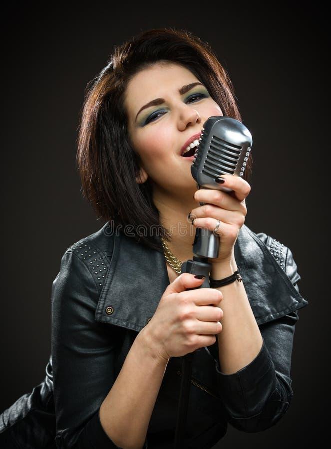 Kobieta rockowy muzyk utrzymuje mic fotografia stock