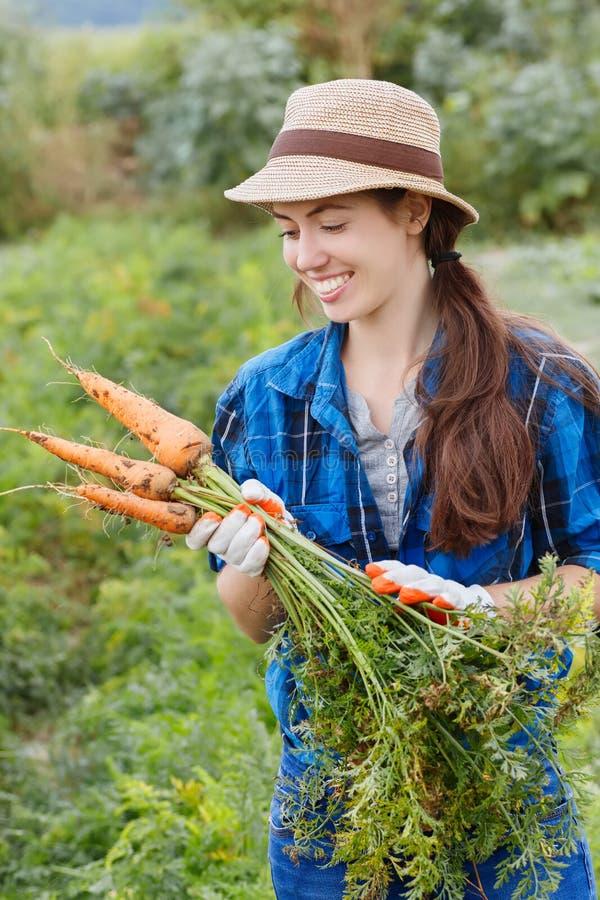 Kobieta rolnik z marchewkami zdjęcie royalty free