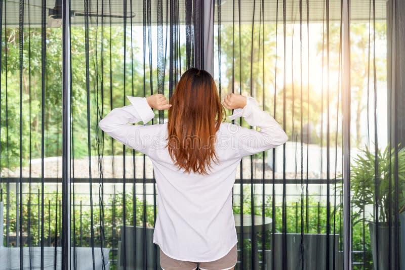 Kobieta rozciąga ona ręki podczas gdy trwanie i przyglądający wschód słońca thr fotografia stock