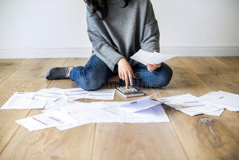 Kobieta rozjaśnia jej rachunki na podłoga obrazy royalty free