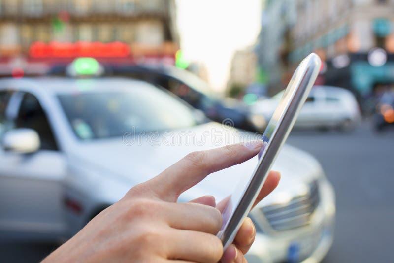 Kobieta rozkazuje taxi od jej telefonu komórkowego obraz stock