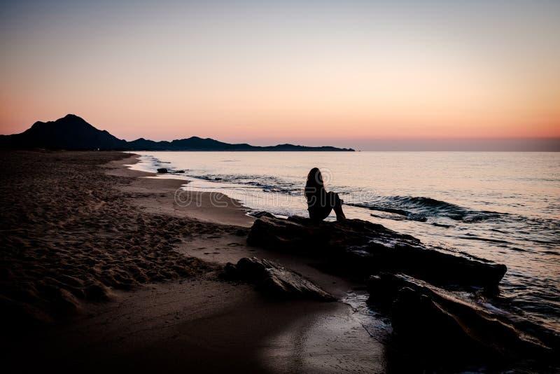 """Kobieta rozmyÅ›lajÄ…ca o wschodzie sÅ'oÅ""""ca na plaży zdjęcie stock"""