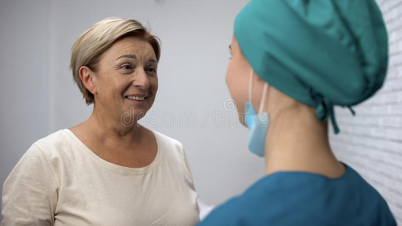 Kobieta słucha dobre wieści od lekarki, czuć szczęśliwy, wyzdrowienie i darowanie, obrazy royalty free