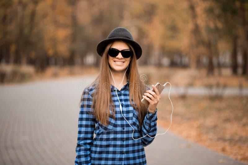 Kobieta słucha muzyka w jesień parku w okularach przeciwsłonecznych cieszyć się muzyki zdjęcia royalty free