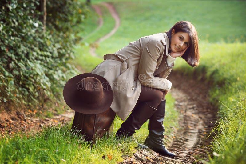 Kobieta sadzająca na rzemiennej walizce obraz stock