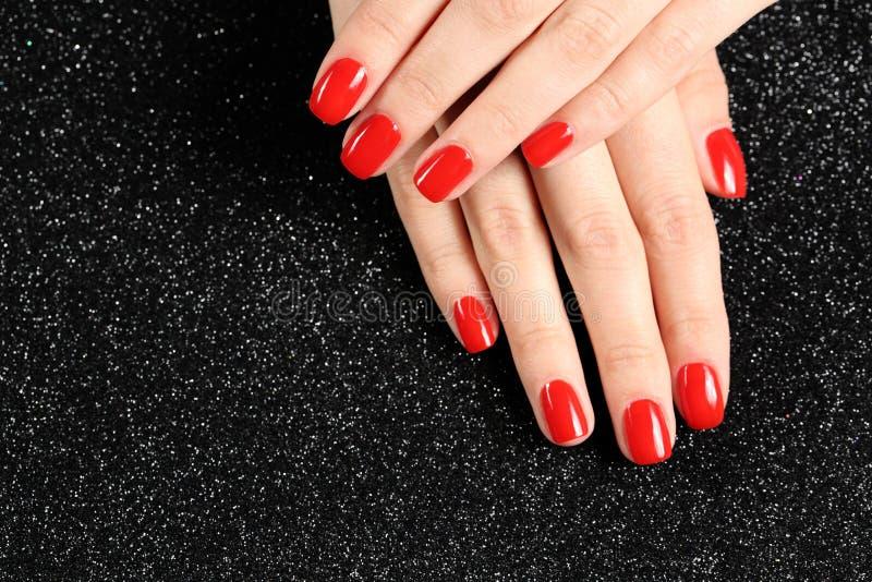 Kobieta seans robił manikiur ręki z czerwonym gwoździa połyskiem na czarnym tle Przestrze? dla teksta obrazy royalty free