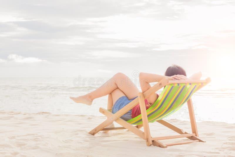 Kobieta sen na plażowym krześle przy midday zdjęcia royalty free