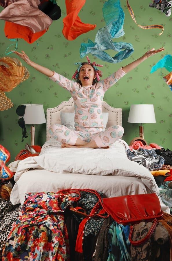 Kobieta siedząca na łóżku rzuca ubrania zdjęcia stock