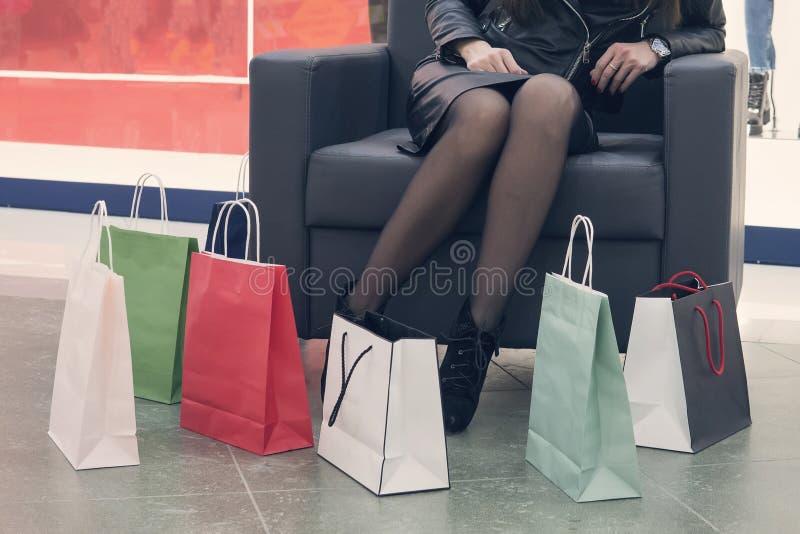 Kobieta siedząca na fotelu w centrum handlowym, kładąca na podłodze torby z papierem na zakupy Kobieta siedząca po zakupach w pob obraz stock