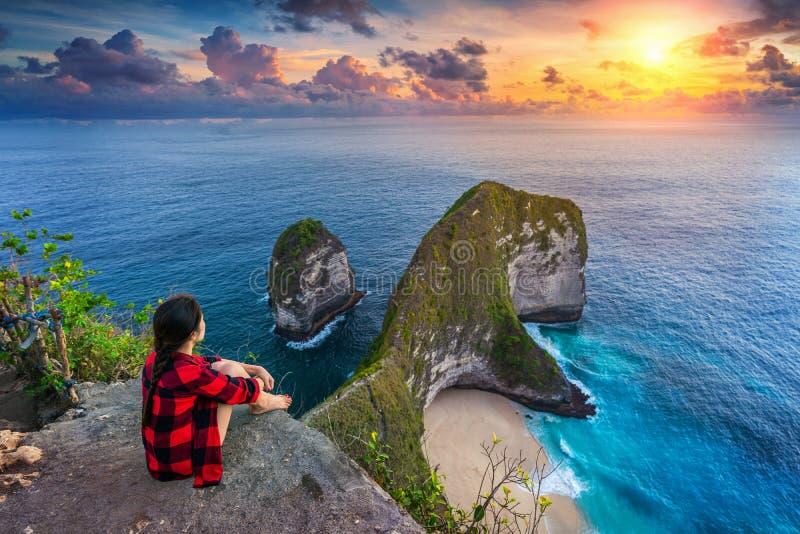 Kobieta siedząca na klifie i patrząca na zachód słońca na plaży Kelingking na wyspie Nusa penida, Bali, Indonezja zdjęcie stock