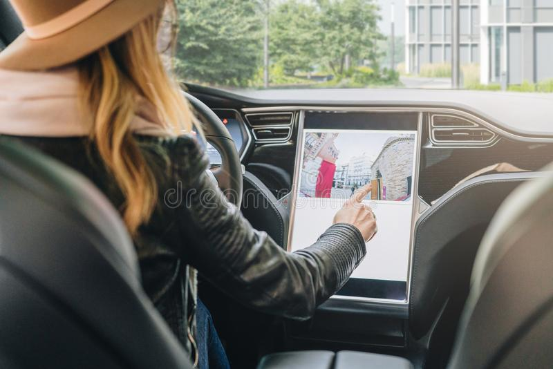 Kobieta siedzi behind toczy wewnątrz samochód i uses elektroniczną deskę rozdzielczą Dziewczyna podróżnik patrzeje dla sposobu pr zdjęcia royalty free