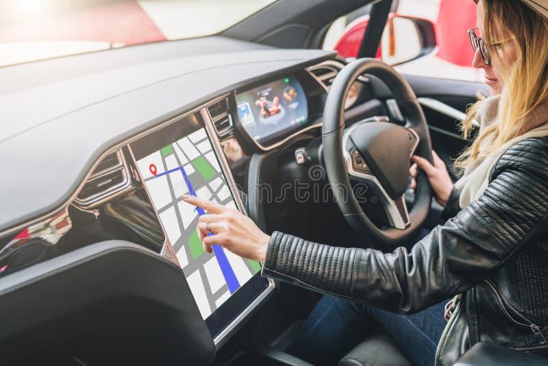 Kobieta siedzi behind toczy wewnątrz samochód i uses elektroniczną deskę rozdzielczą Dziewczyna podróżnik patrzeje dla sposobu pr zdjęcie stock