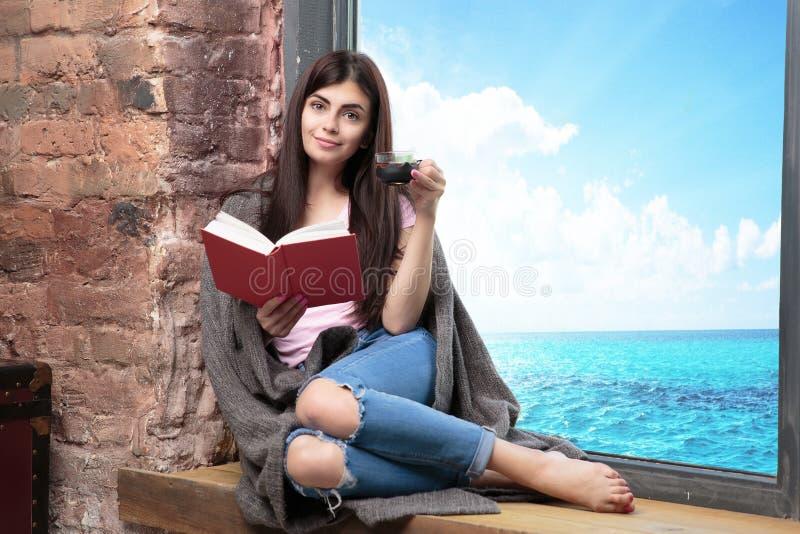 Kobieta siedzi blisko nadokienny relaksować w jej żywej izbowej czytelniczej książce i pić w domu kawę lub herbaty obraz stock