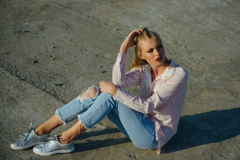 Kobieta siedzi na cement ziemi, moda obraz stock