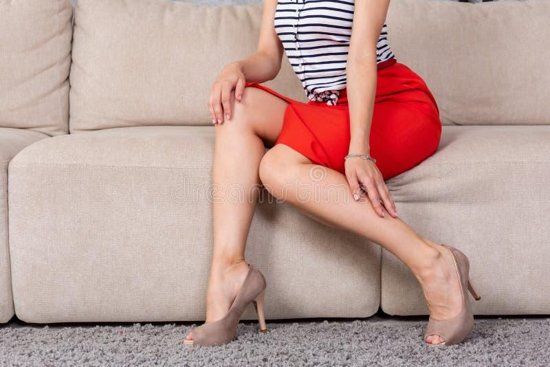 Kobieta siedzi na leżance w modnych krótkich sukni spódnicy szpilkach fotografia royalty free