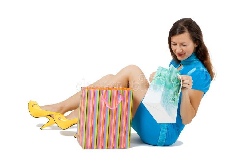 Kobieta siedzi na podłoga z pakunkami zdjęcia stock