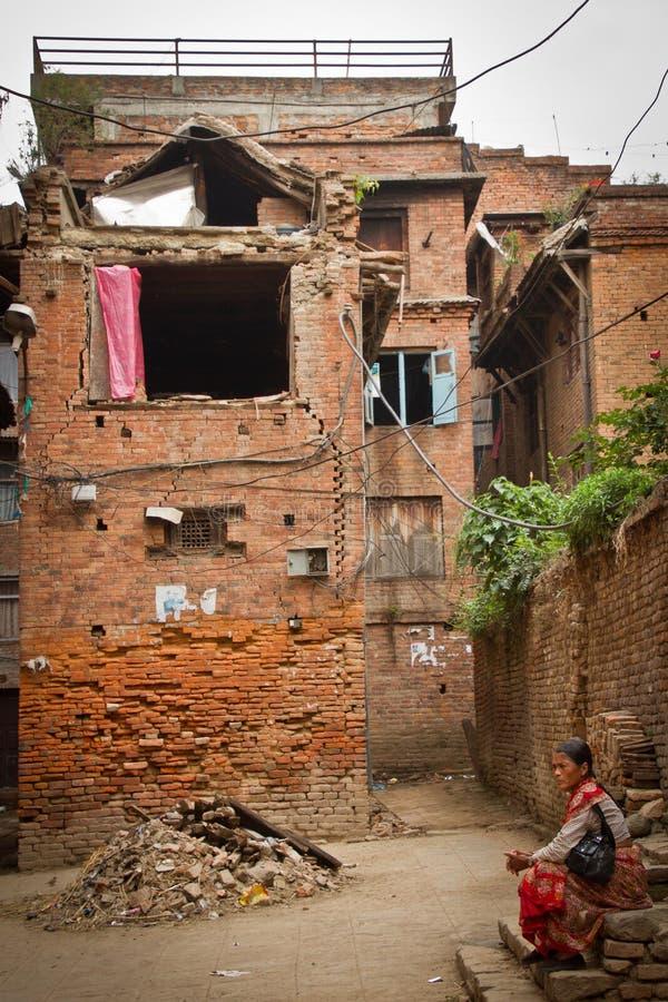 Kobieta siedzi na zewnątrz jej trzęsienie ziemi rujnującego domu w Bhaktapu teraz fotografia royalty free