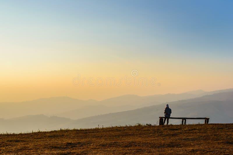 Kobieta siedzi nad halnym wierzchołkiem zdjęcia stock