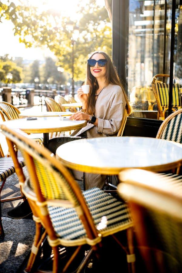 Kobieta siedzi outdoors przy francuską kawiarnią zdjęcia royalty free