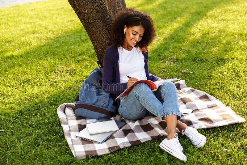 Kobieta siedzi outdoors w parkowych writing notatkach w copybook słuchającej muzyce z słuchawkami zdjęcia royalty free