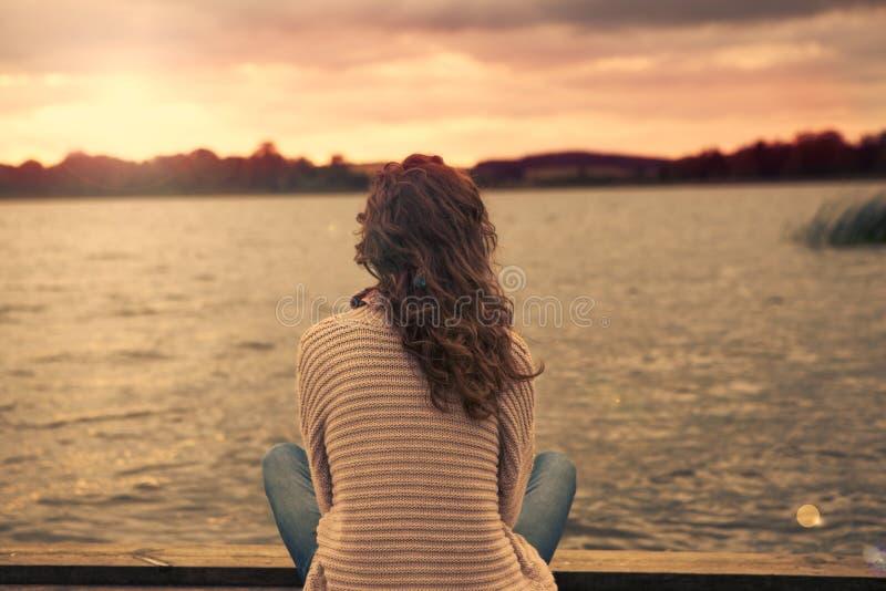 Kobieta siedzi przy jeziorem obraz stock