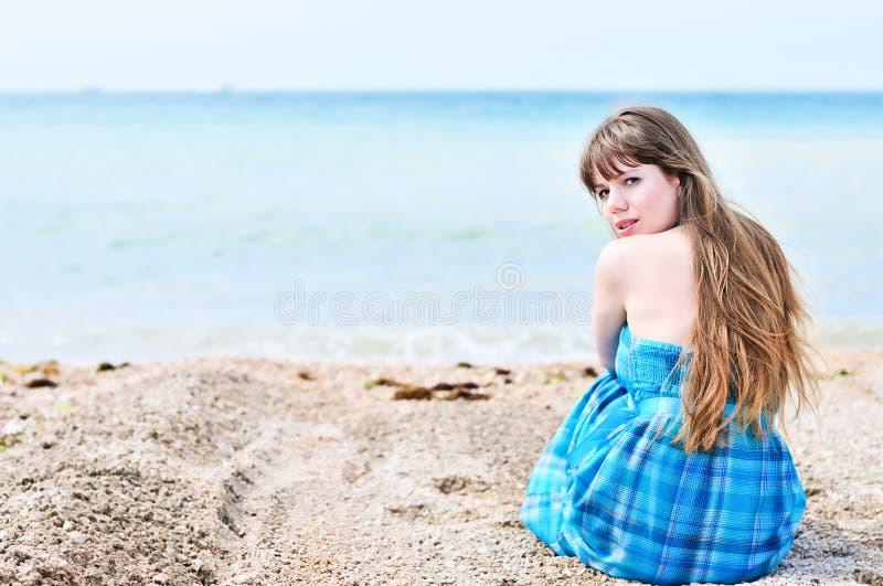 Kobieta siedzi samotnie przy plażą fotografia royalty free