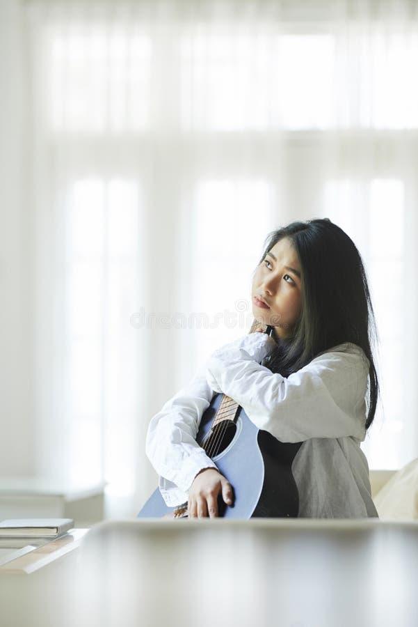 Kobieta siedzi w domu z gitarą fotografia stock