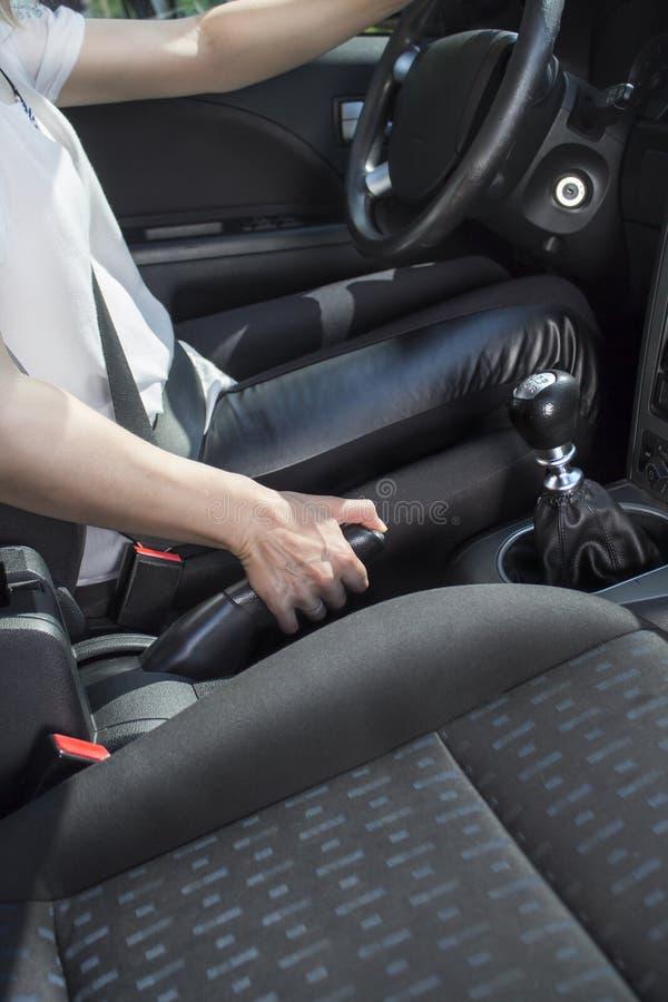 Kobieta siedzi za kołem samochód osobowy i ciągnie handbrake zdjęcia royalty free