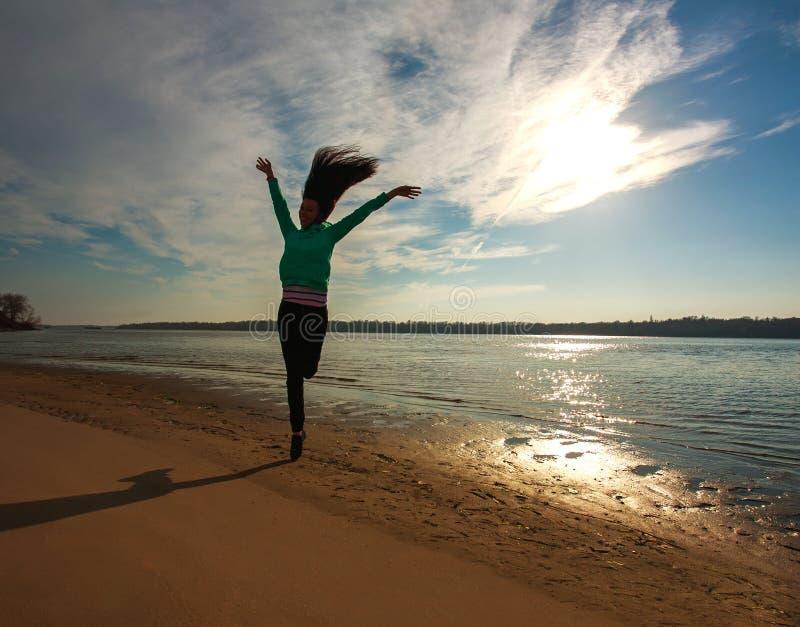 Kobieta skacze na plaży na wschodu słońca nieba tle, wolności pojęcie zdjęcie stock