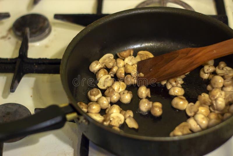 Kobieta smaży pieczarki w kuchni Proces smażyć w smaży niecce Przygotowanie jedzenie receptą Domowy kitch zdjęcia stock