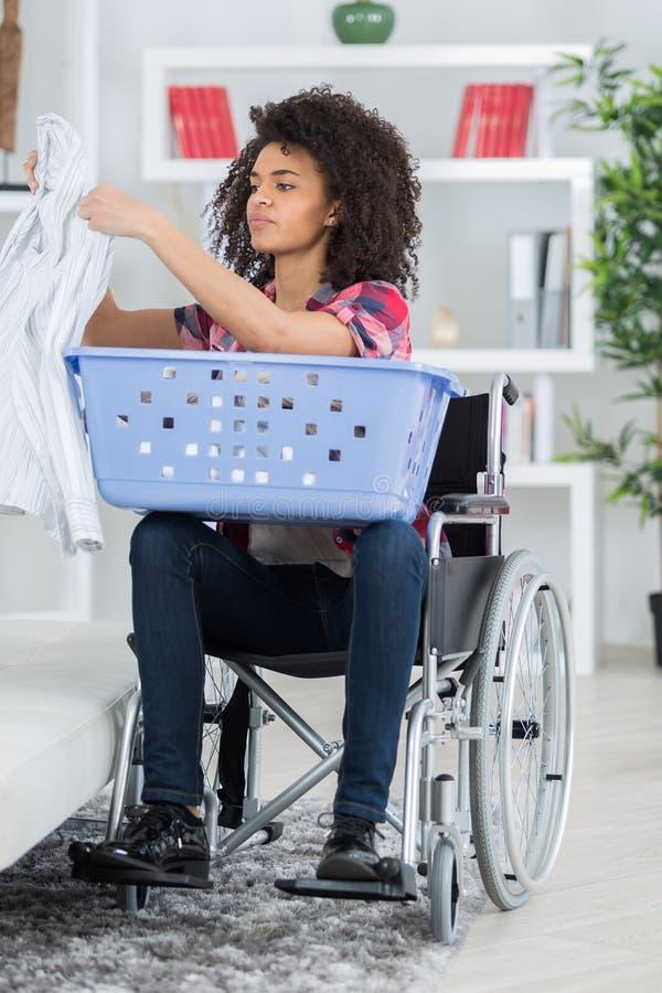 Kobieta sortuje pralnię na wózku inwalidzkim zdjęcie royalty free