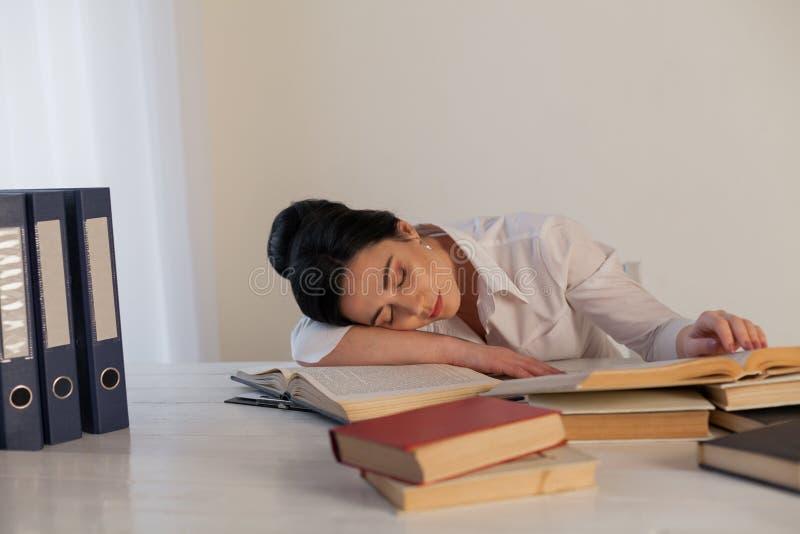 Kobieta spadał uśpiony przy stołowym czytaniem książka zdjęcie royalty free