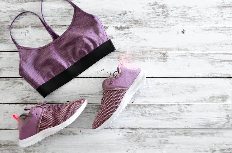 Kobieta sporta sneakers na drewnianym tle z odbitkowym zdrojem i stanik fotografia stock