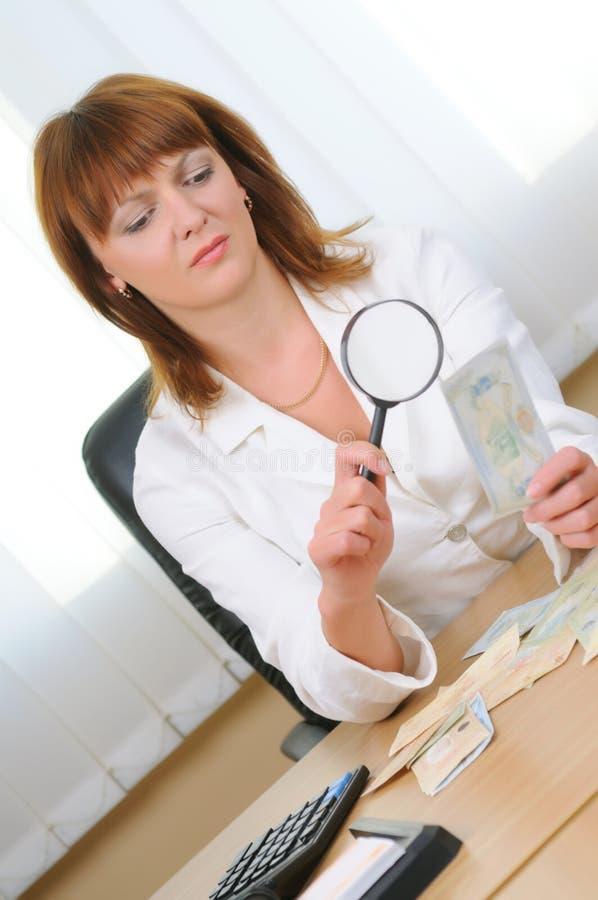 Kobieta sprawdza autentyczność rachunku zdjęcie royalty free
