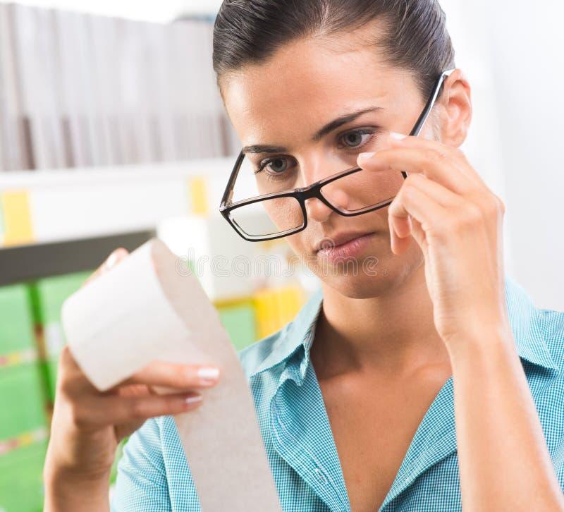 Kobieta sprawdza kwit z szkłami zdjęcie stock