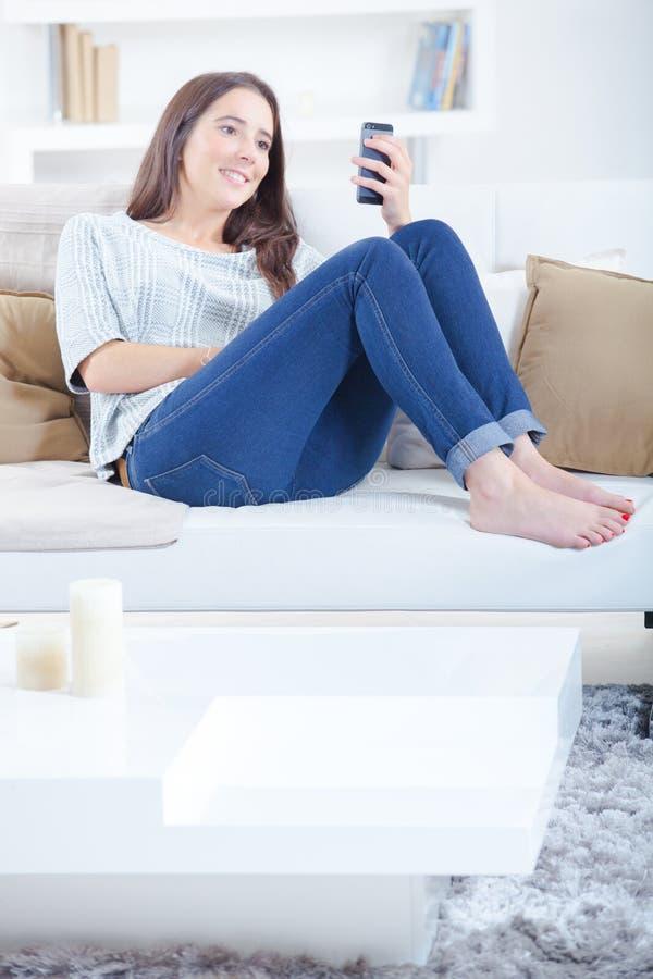 Kobieta sprawdza smartphone na kanapie fotografia royalty free