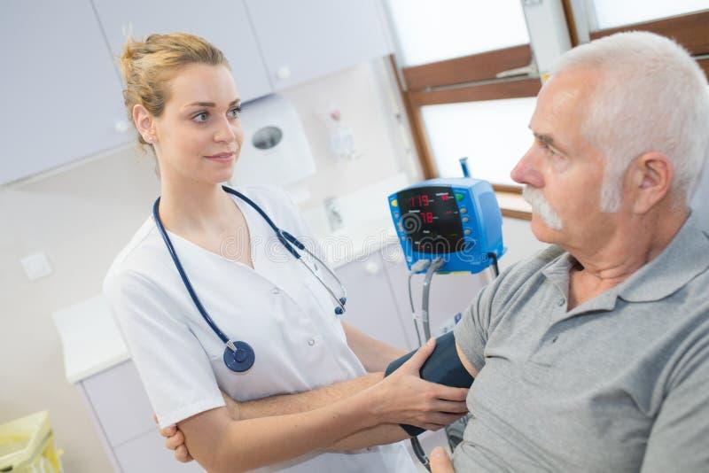 Kobieta starego człowieka doktorski sprawdza cierpliwy arterialny ciśnienie krwi obraz stock