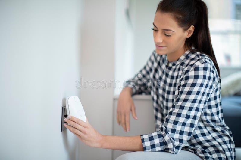 Kobieta Stawia Mądrze prymkę W władzy nasadkę W Domu zdjęcie stock