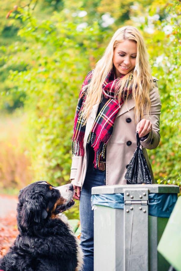 Kobieta stawia mnie w kosz na śmiecie podnosi up psiego poo obraz stock