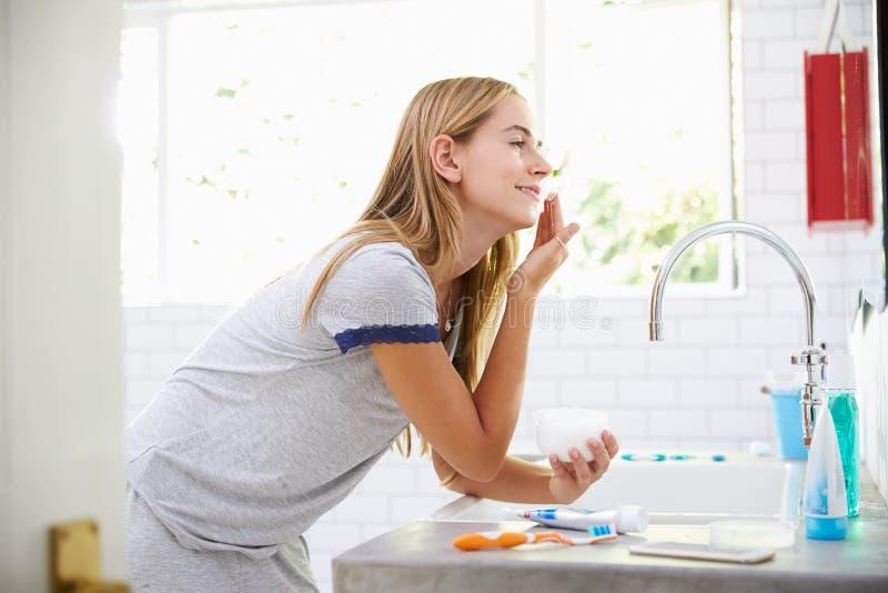 Kobieta Stawia Na Moisturizer W łazience W piżamach fotografia royalty free
