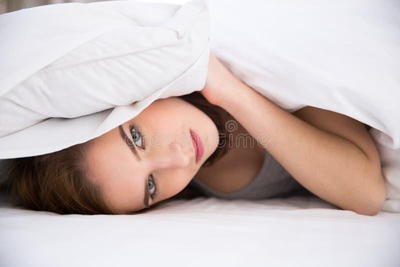 Kobieta stawia poduszkę nad jej głową zdjęcia stock
