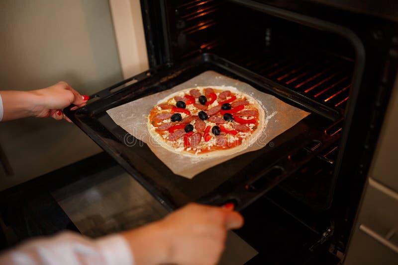 Kobieta stawia Surową pizzę z składnikami i pomidorem, pikantność, kiełbasa obraz stock