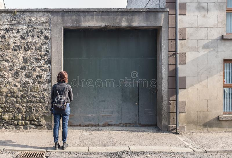 Kobieta stoi bezczynnie dziwacznego wejściowego drzwi obraz royalty free