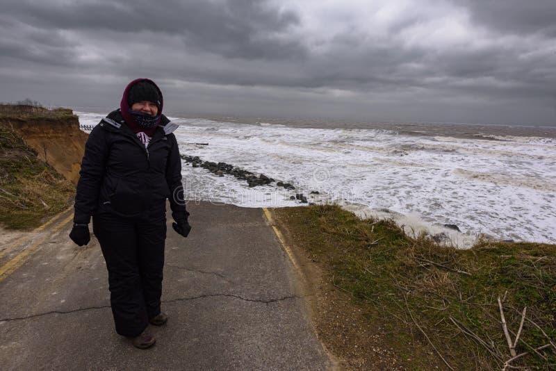 Kobieta stoi bezczynnie Nabrzeżną erozję ma miejsce podczas zimy burzy Wiele domy ostatnio gubili w ten społeczności należnej zdjęcia royalty free