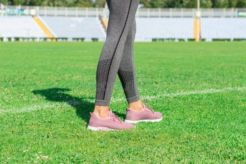 Kobieta stoi na boisku piłkarskim z białą linią z różowymi sneakers przygotowywa dla biegać na stadium obrazy stock