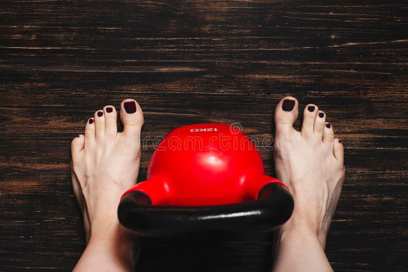 Kobieta stoi nagą stopę z czerwonym kettlebell między ona nogi zdjęcia stock