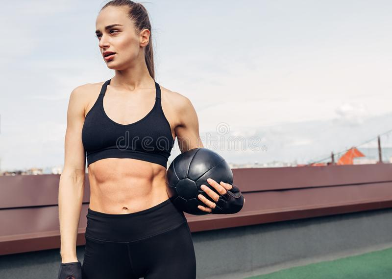 Kobieta stoi outdoors na tarasie z medycyny piłką w sprawności fizycznej odzieży fotografia royalty free