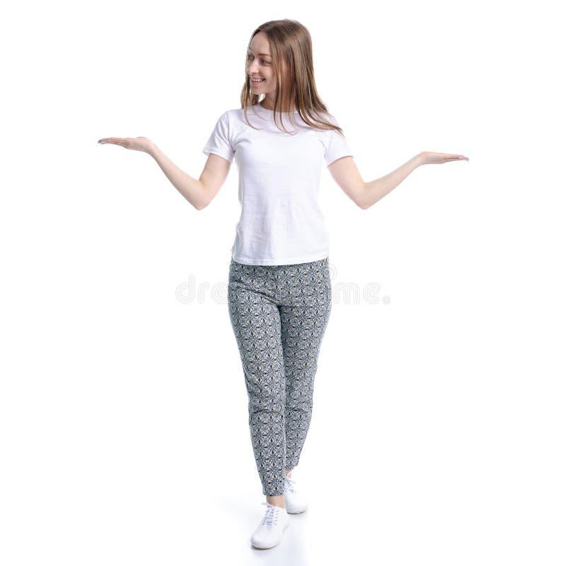 Kobieta stoi uśmiecha się w białych spodniach i koszulce pokazywać wskazywać obrazy stock