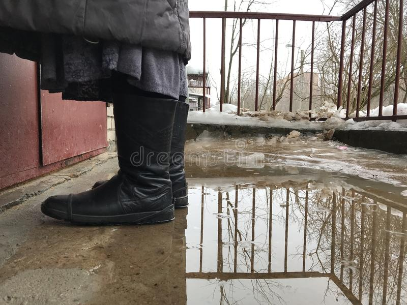 Kobieta stoi w kałuży przed drzwi w butach zdjęcia royalty free